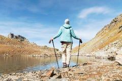 有跟踪的棍子一个苗条女孩背包徒步旅行者在一个高山湖旁边站立高在高加索的山 库存照片