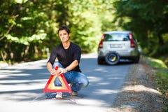 有路旁划分的他的汽车的英俊的年轻人 库存图片