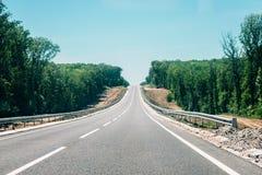有路旁工地工作的新的柏油路森林乡下柏油路重建的 库存照片
