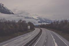 有路旁树的路对山在烟特勒根 免版税库存照片