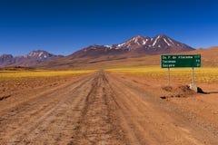 有路标的土路和山在背景中,在阿塔卡马沙漠,智利 免版税库存图片