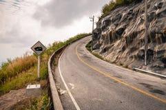 有路标的绞的山柏油路对天空 库存图片