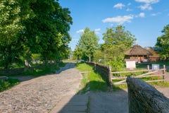 有路的一条古老农村街道铺与有站立在庭院里的木房子的鹅卵石操刀与a 图库摄影