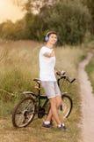 有路的可爱的年轻微笑的人骑自行车户外 免版税库存照片