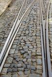 有路轨叉子的里斯本高倾斜街道 免版税库存照片
