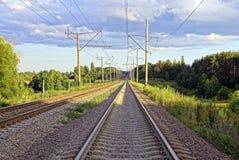 有路轨和睡眠者的空的铁路在植被中 库存照片