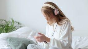 有跳舞和听到在沙发的音乐的耳机的愉快的年轻女人 股票视频
