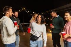 有跳舞在屋顶党的饮料的朋友 免版税图库摄影