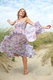 有跳舞的妇女与在海滩的夏天礼服 免版税图库摄影