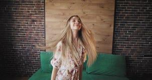 有跳舞长的金发的可爱的夫人跳跃和吸引人在都市单室公寓的照相机前面 股票录像