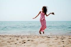 有跳跃在一个热带海滩的长的桃红色礼服的美丽的妇女 库存照片
