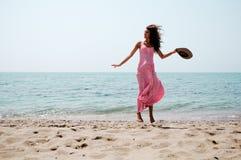 有跳跃在一个热带海滩的长的桃红色礼服的美丽的妇女 库存图片