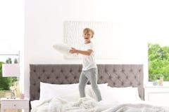 有跳跃在床上的枕头的逗人喜爱的小男孩 图库摄影