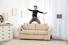 有跳跃在沙发的话筒的逗人喜爱的男孩 图库摄影