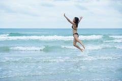 有跳跃在海滩和w的棕色泳装比基尼泳装的秀丽妇女 免版税库存照片