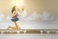 有跳跃在海边的泳装的妇女 免版税库存照片