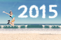 有跳跃在海滩的运动服的妇女 免版税库存照片