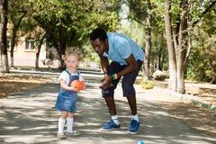 有踢在自然的小女孩的年轻非裔美国人的神父亲橄榄球在夏天 库存照片
