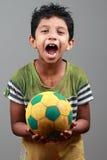 有身体的男孩抹上与泥举行橄榄球并且显示能量 库存照片