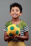 有身体的男孩抹上与泥举行橄榄球并且显示能量 免版税库存图片