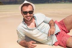 有躺下在海滩的帽子和太阳镜的人 免版税库存照片