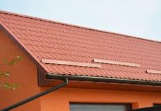 有车库的修造的现代议院建筑,金属屋顶、雨天沟管道系统和屋顶保护免受雪上,下雪 免版税库存照片