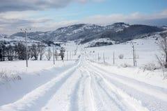 有车滑动的足迹和好的透视的雪道 库存图片