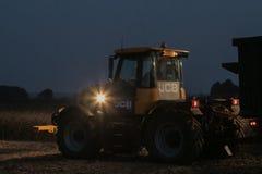 有车灯的拖拉机在夜间 库存图片