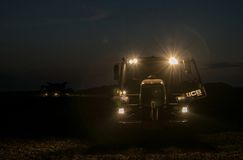 有车灯的拖拉机在夜间 免版税图库摄影