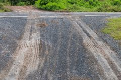 有车轮踪影的湿石渣路 免版税库存图片