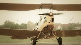 有转动的推进器指点的葡萄酒双翼飞机在地面 股票视频