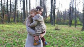 有转动的婴孩的母亲  走室外在秋天公园 股票视频