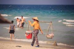 有轭的供营商沿海洋海滩走反对游人 库存图片