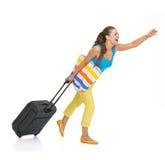 有轮子袋子传染性的出租汽车的年轻旅游妇女 免版税库存照片