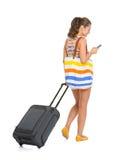 有轮子袋子文字sms的年轻旅游妇女。背面图 库存照片