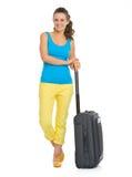 有轮子袋子的微笑的年轻旅游妇女 免版税库存图片
