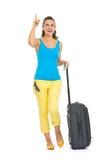 有轮子袋子的愉快的年轻旅游妇女指向在拷贝空间的 免版税库存图片