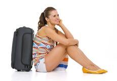 有轮子袋子的年轻旅游妇女坐地板 库存照片