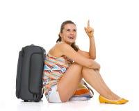 有轮子袋子的年轻旅游妇女坐地板 库存图片