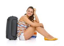 有轮子袋子的年轻旅游妇女坐地板 免版税库存照片