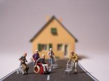 有轮椅和步行者的Minitature资深人民在街道不理会 库存照片