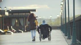 有轮椅的一起走在码头的残疾人的年轻愉快的妇女 股票录像