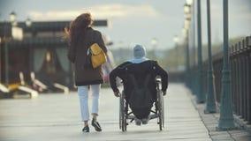 有轮椅的一起走在码头的残疾人的年轻愉快的妇女 影视素材