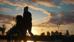 有轮椅的走通过码头的残疾妇女的有同情心的人在日落 影视素材