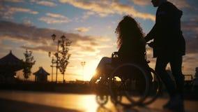 有轮椅的走通过码头的残疾妇女的有同情心的人在日落 股票视频