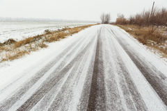 有轮胎轨道的冬天路在雪以后 库存照片