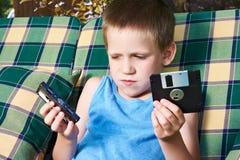 有软盘和卡型盒式录音机的小男孩 免版税库存照片
