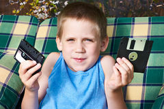 有软盘和卡型盒式录音机的小男孩 库存照片