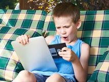 有软盘和片剂个人计算机的小男孩 免版税库存图片