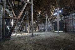 有轻发光的老木谷仓通过木板 库存图片